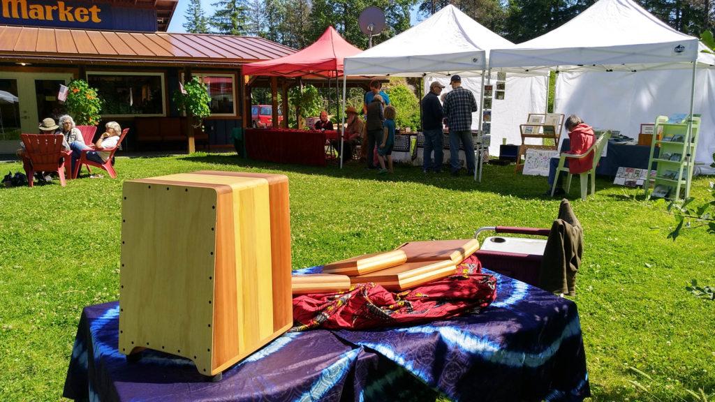Cajon em uma mesa com outras mesas vendendo itens em uma feira de artesanato.